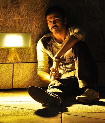 Fine photographer Niyaz Ahmed sitting floor illuminated by single table lamp.