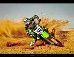Rider on dirt bike leaning heavily to right and throwing up bunch of sand.