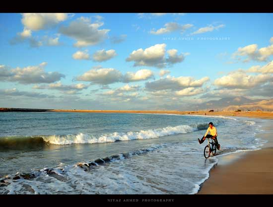 Man on bicycle feet up riding on beach as new wave rolls in with blue cloudy sky.